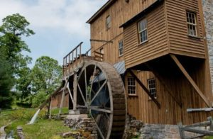 Wooden mill with large wheel next to a stream