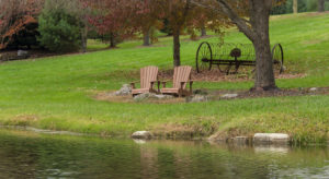 Front view of adirondack chairs sitting by a pond on the grass
