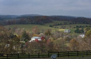 Rolling country hills and fall foliage with a split-rail fence