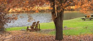 Two Adirondack chairs by a pond with fall foliage in the background at Steeles Tavern Manor B&B