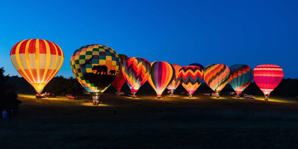 Hot Air Balloons at dusk with their fires burning to create a glow.