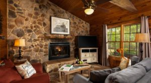 view of sitting room with stone wall, fireplace, and TV
