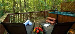 hot ub and lounge chairs on the deck of a cabin with a view of the forest